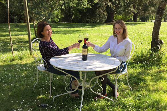 Photo of two women tasting some wine.
